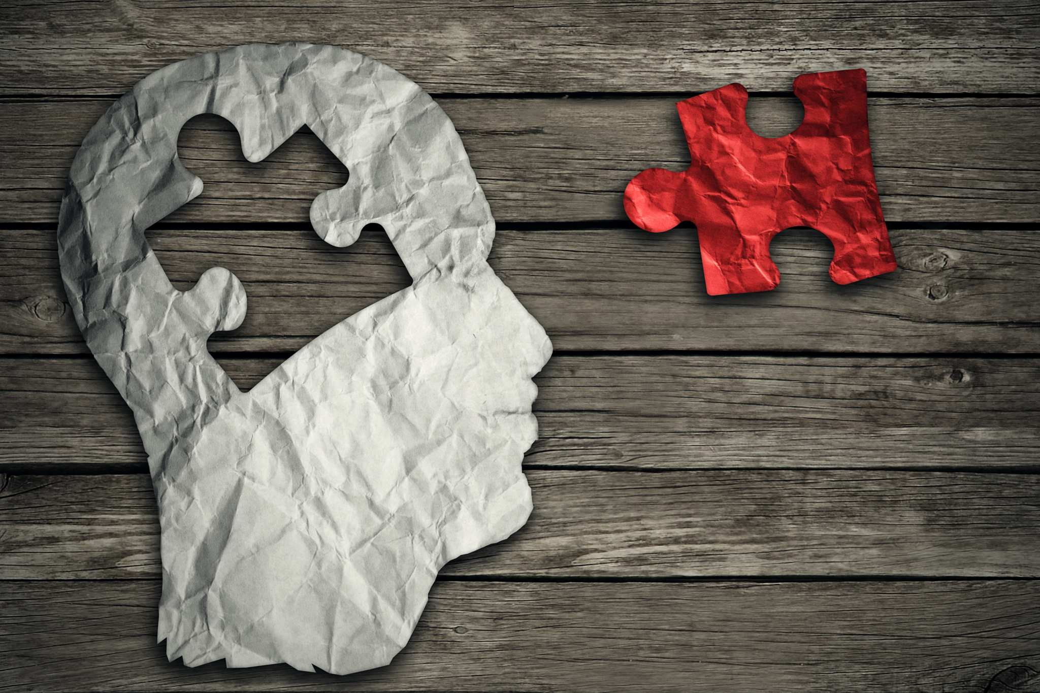 A white paper cutout of a human head, missing a puzzle piece shaped hole, sits on a wooden surface. The puzzle piece, colored red, sits nearby. Though still theoretical, clinical endocannabinoid deficiency could be a common contributor to numerous conditions, from fibromyalgia to migraines.