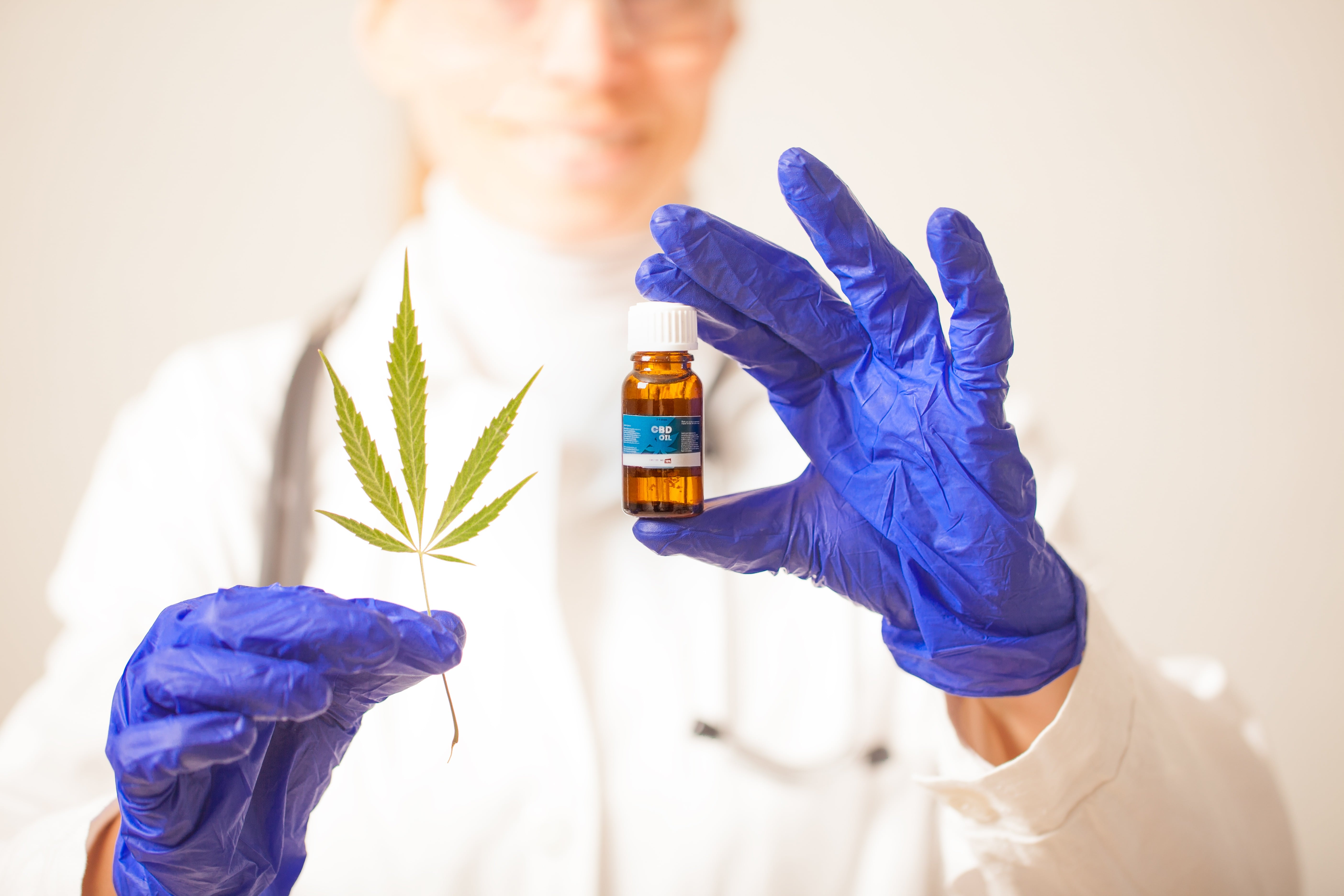 A gloved scientist with a vial of CBD and a hemp leaf. 'Full spectrum' extracts contain more cannabinoids, terpenes, and other beneficial chemicals found in hemp & cannabis.
