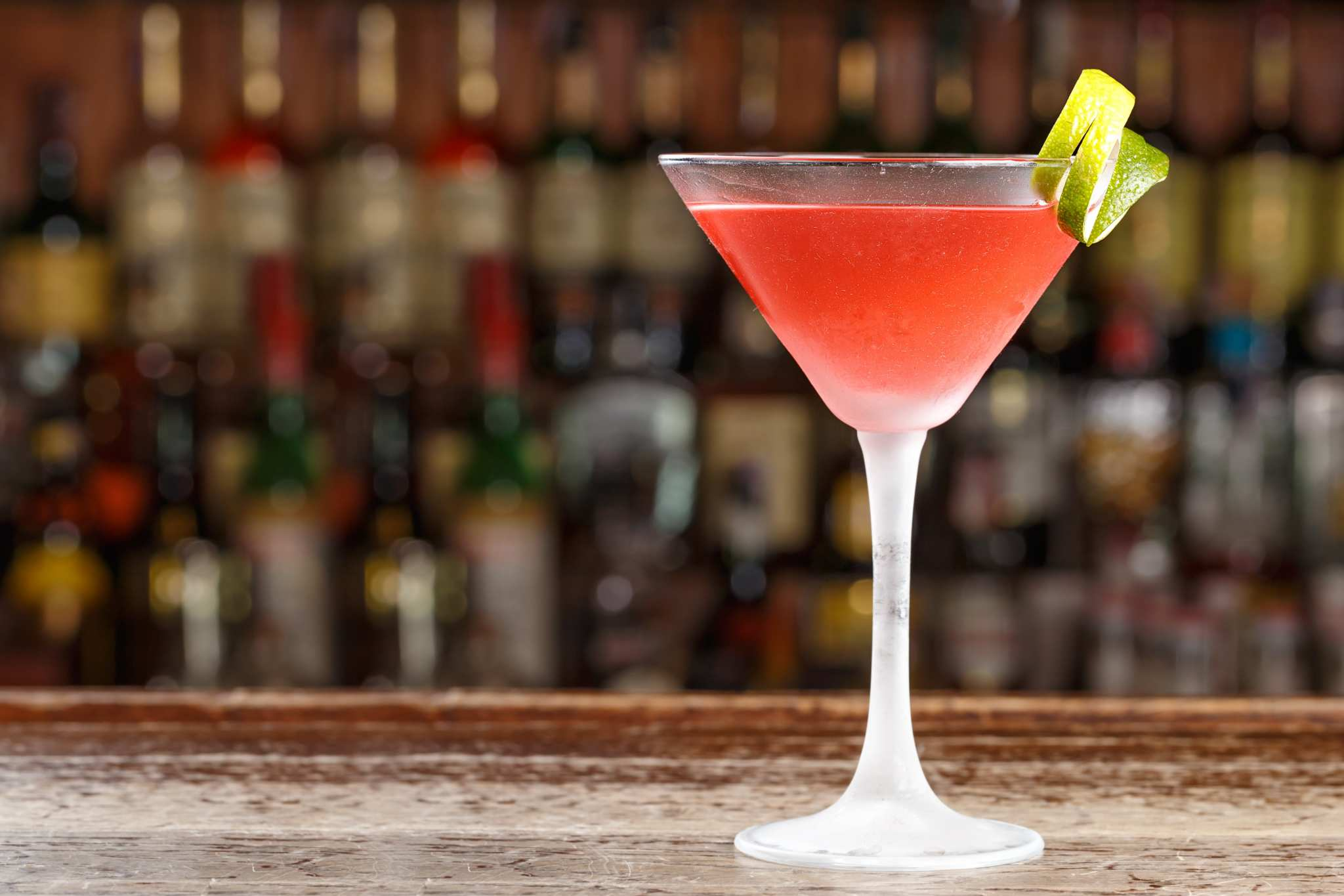 You can start with our CBD-infused Cosmo recipe, but don't be afraid to experiment. The potential of CBD cocktails is nearly endless. A red cocktail in a martini glass, garnished with a lemon peel, sits on a fancy bar with shelves of alcohol in the background.