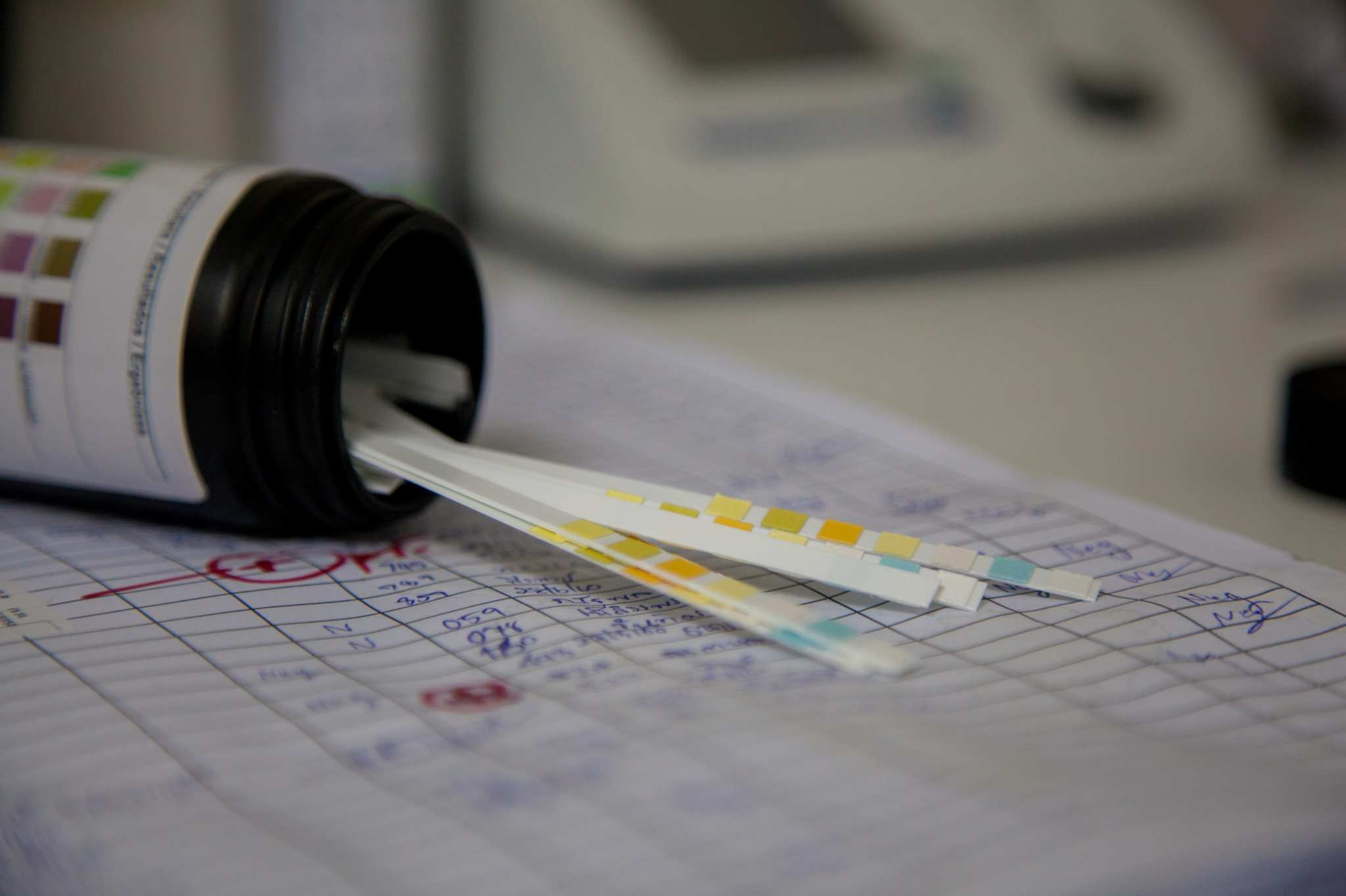 Drug urine test strips spill out onto a page of medical records. Contrary to some beliefs about drug tests and CBD, it is possible but rare for CBD oil to cause someone to fail a drug test.