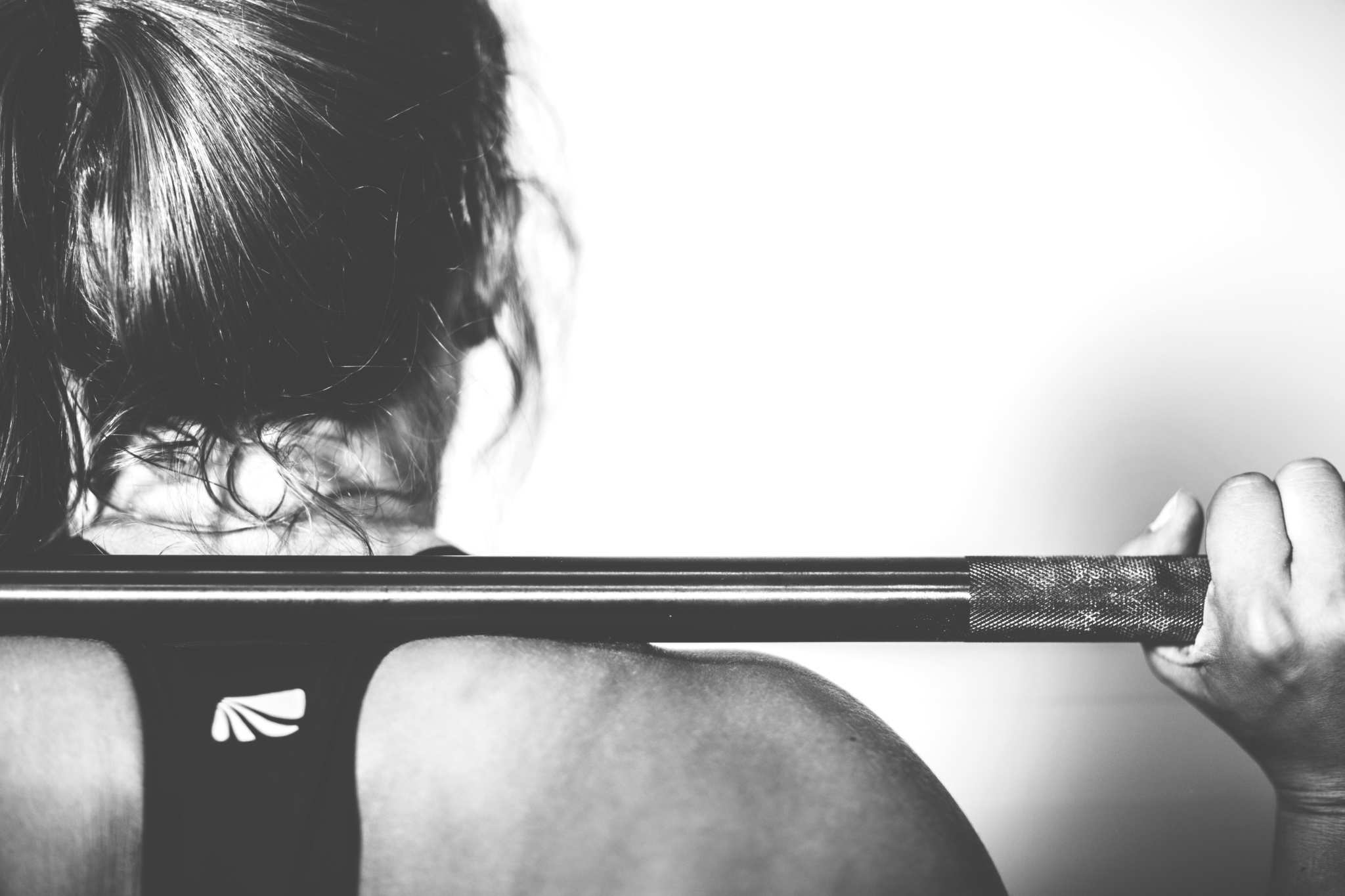 A woman seen from behind holding a weight on her shoulders. Some top athletes are now working out with CBD. CBD oil can reduce the effects of anxiety and promote more restful sleep, all of which promote a better workout.