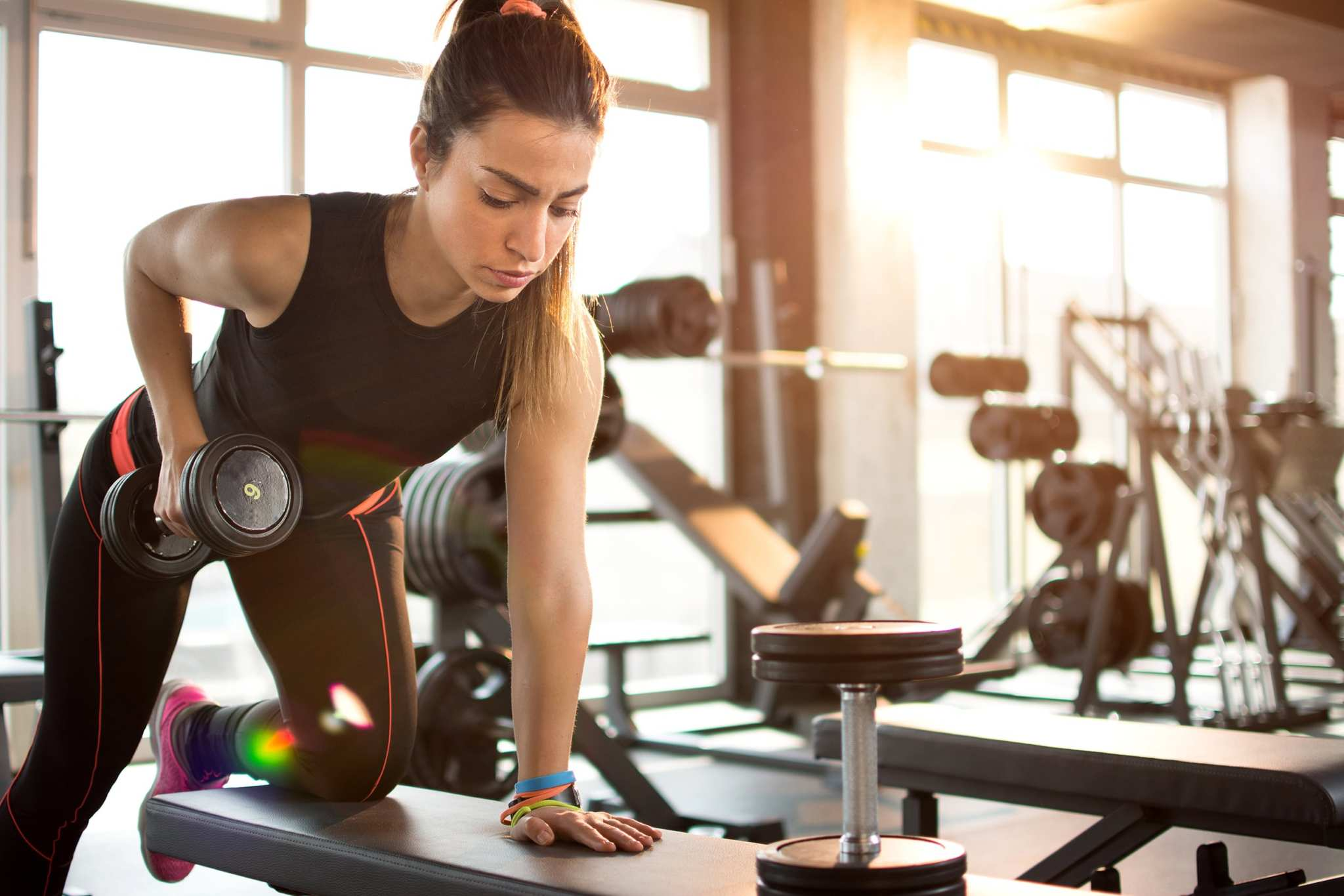 A woman works out with handheld weights in a gym.