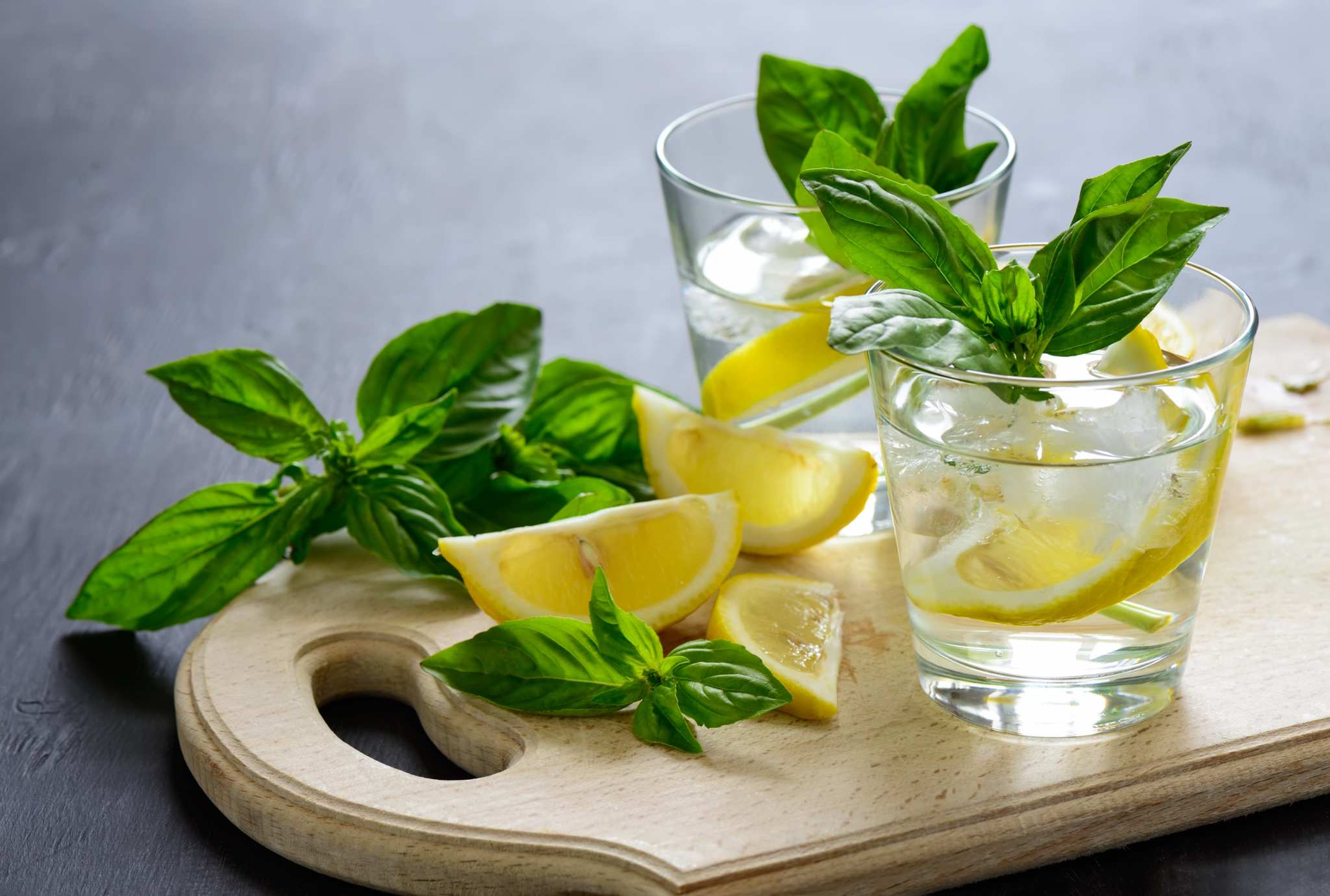 CBD drinks can help you unwind after a long day. A cutting board with lemons, basil and two lowball glasses of basil lemonade.