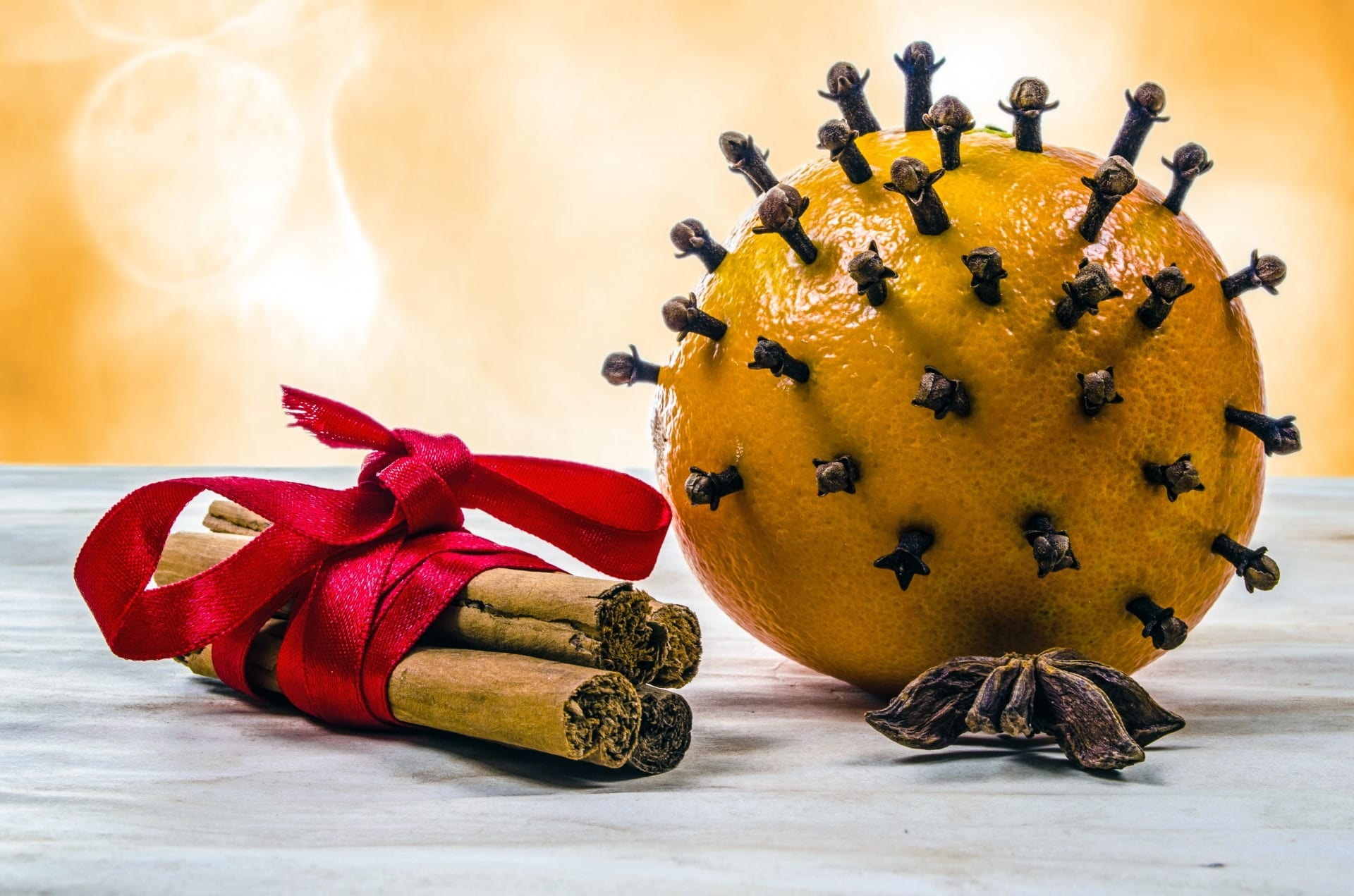A bundle of cinnamon sticks in a ribbon sits next to a clove orange. Cinnamon sticks and a clove orange help enhance the warm apple and hemp flavors of our CBD mulled apple cider.