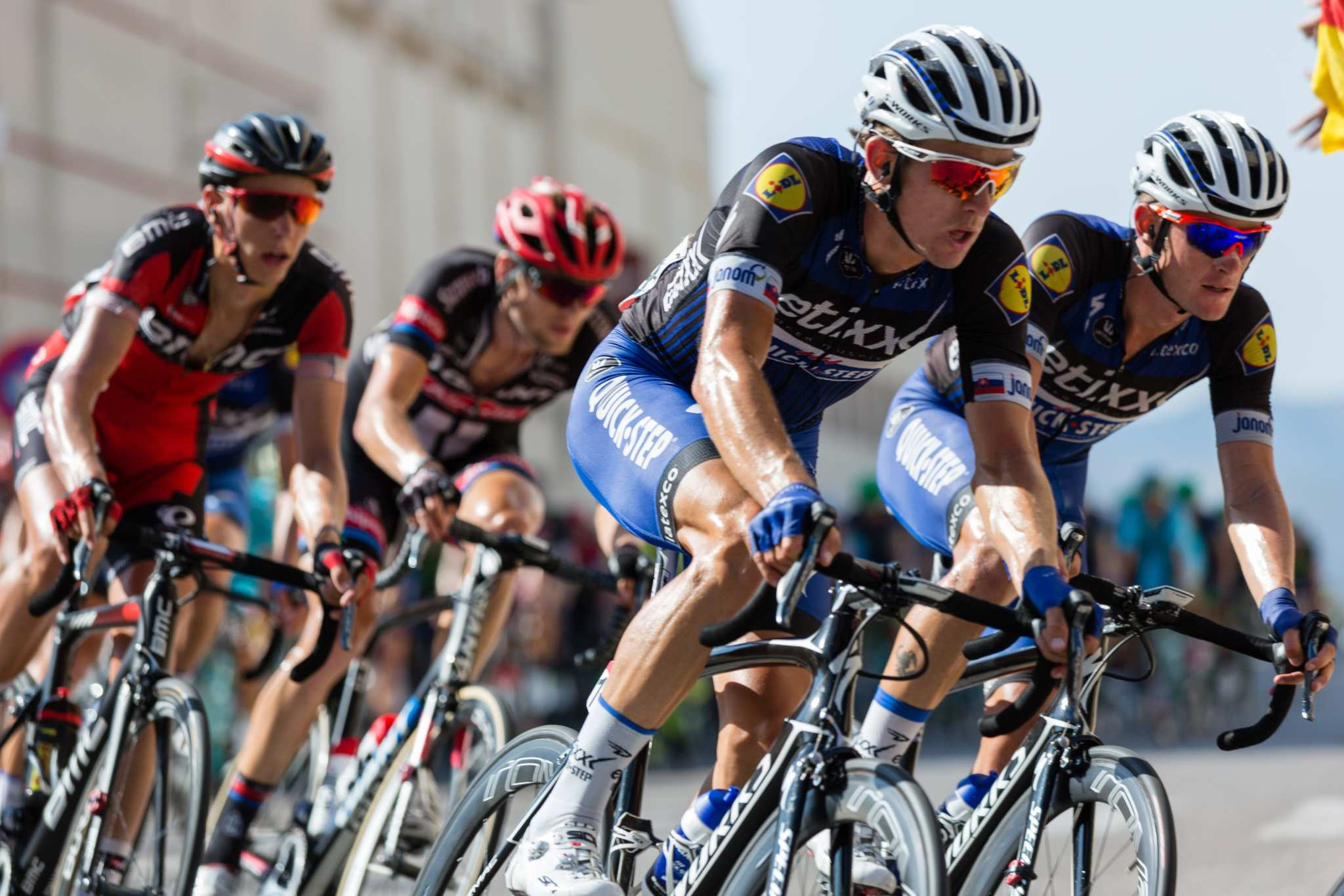 Cyclists race on a roadway in a tight pack, wearing sponsored pro cyclist gear and helmets. Some endurance athletes use CBD to reduce their dependence on pharmaceutical painkillers to relieve the soreness of workouts.