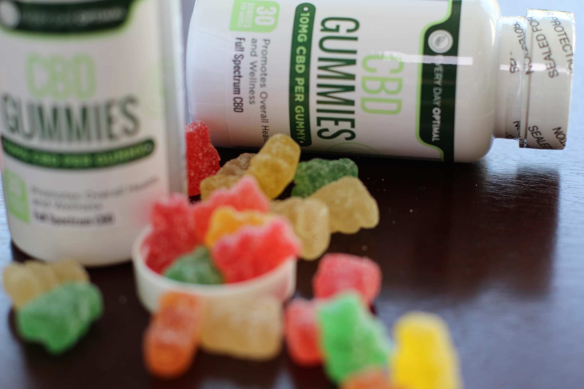 A pile of Every Day Optimal CBD gummies spill from gummy bottle, while another bottle of gummies lies nearby. the cap of a Every Day Optimal CBD gummies, available in 25mg strength, pack potent CBD relief into a delicious sweet & sour candy.