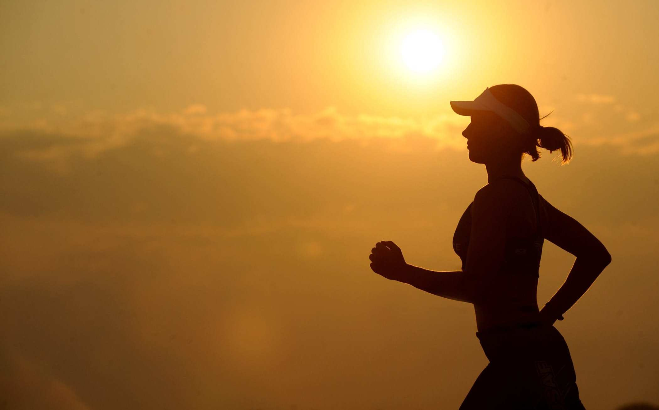 A silhouette of a runner jogging during a sunrise. Distance runners, triathletes, professional cyclists and other endurance athletes use CBD because it helps them perform better and longer.