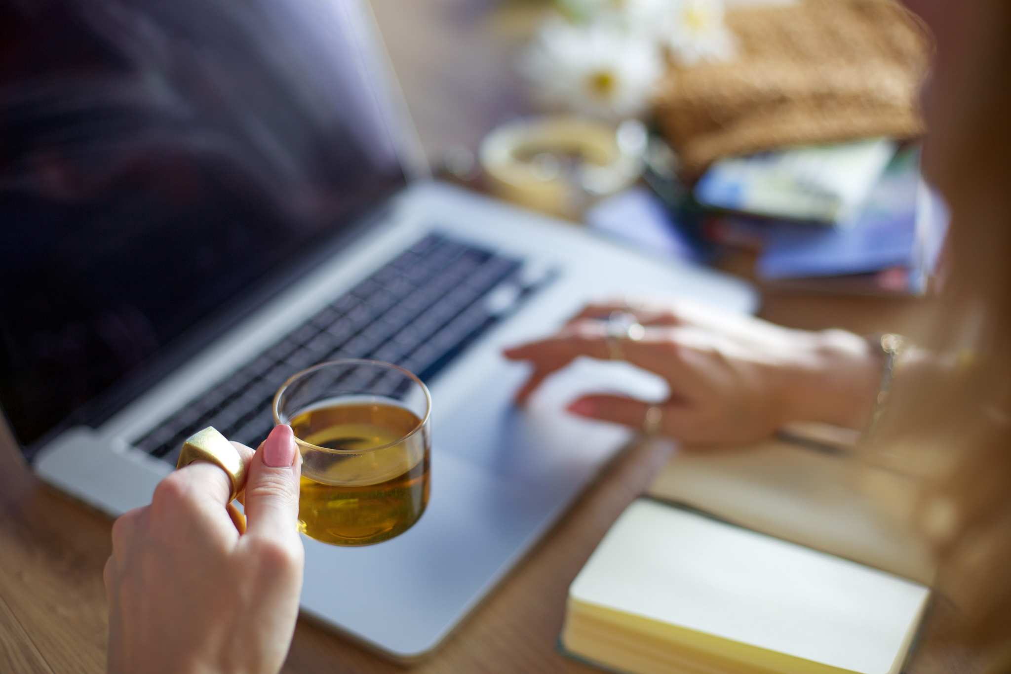 A woman drinks a cup of tea as she shops online with a laptop. A notebook is open in front of the keyboard. Ministry of Hemp partnered with our favorite brands to bring you great Black Friday CBD deals, so you can restock, try new products, and share CBD with your loved ones.