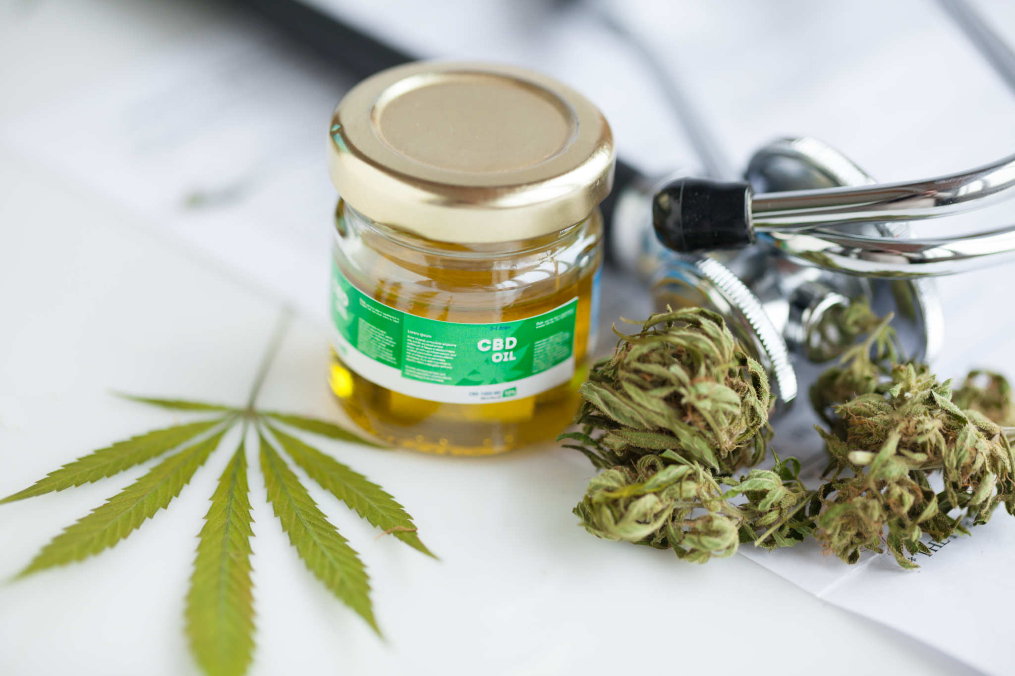 A stethoscope rests near a hemp leaf, some hemp flower buds, and a jar of CBD oil. Although CBD is widely recognized as safe, many medical professionals are still reluctant to recommend it. Patients are often forced to research CBD for themselves.