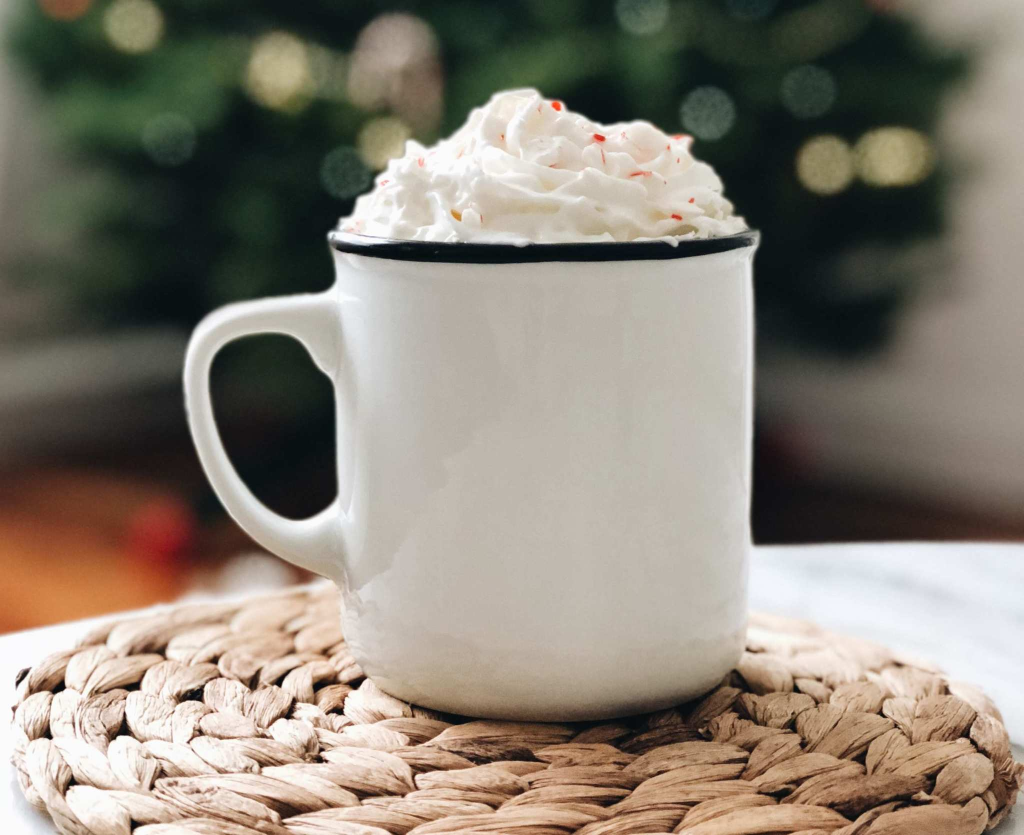 A mug of hot chocolate with whip cream, with a Christmas tree in the background. Our CBD hot cocoa recipe will warm you up and soothe away the stress of chasing the perfect gifts.