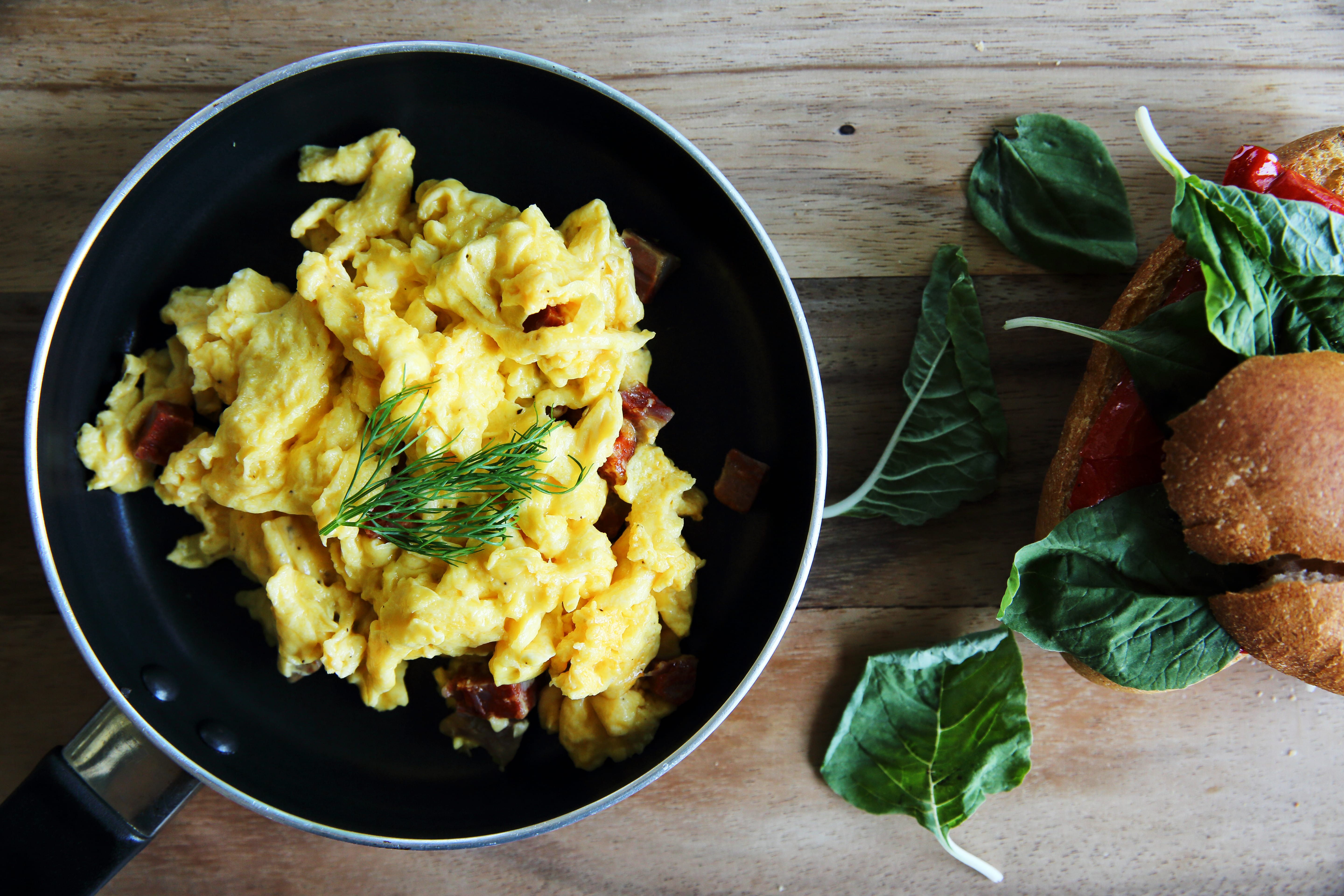 A pan of scrambled eggs with added herbs. Creating a delicious hemp breakfast might be as simple as adding hemp hearts or infusing CBD oil into the butter you use to make eggs.