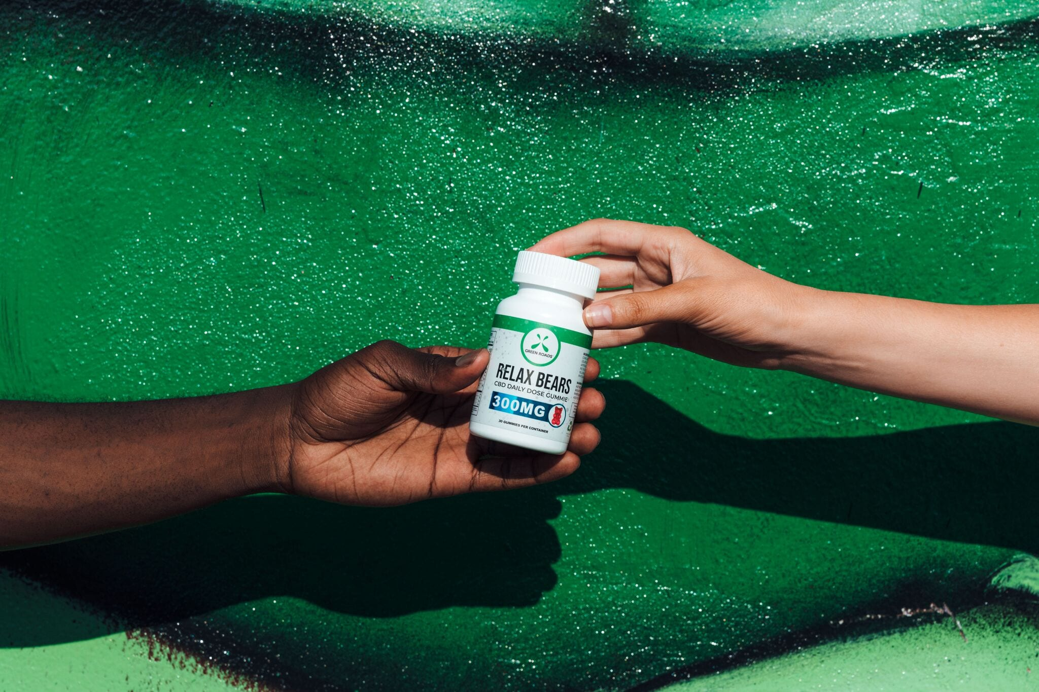 One person, seen from just the arm and hand, as they pass off a bottle of Green Roads Relax Bears to a friend, hand-to-hand. Green Roads Relax Bears combined CBD oil with a sweet taste in a convenient, chewy shape.