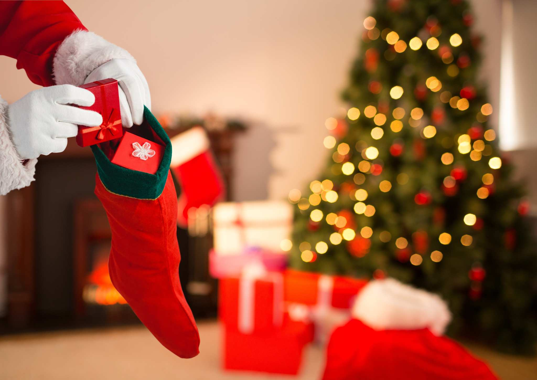 Someone in a santa costume, seen as just a pair of gloved hands in a red coat, packs small gifts into a stocking. There's a tree with presents in the background. Ministry Of Hemp's Holiday Hemp & CBD Gift Guide can help you share the gift of hemp with your family and friends.