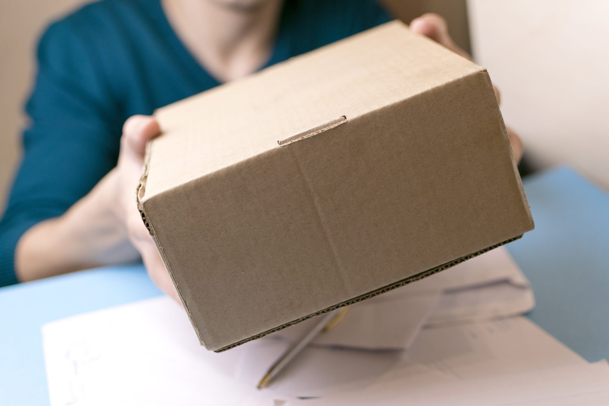 Point of view photo of a person mailing a cardboard box hands it off to a worker. Although there may continue to be court challenges, recent court rulings clearly establish a solid precedent making it legal to send hemp by mail.