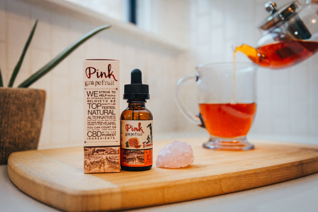 A bottle of Savage CBD Pink Grapefruit CBD Tincture, with accompanying box, sits on a cutting board while a cup of tea is poured into an nearby mug. With its fresh fruit taste, Savage CBD Pink Grapefruit Tincture makes a great addition to tea and CBD cocktails.