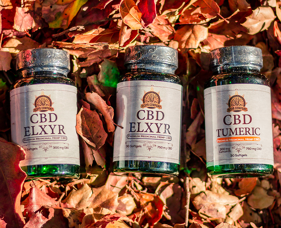 Elxyr CBD Softgels in two strengths, both with and without turmeric. The bottles are posed against a natural, leafy background.