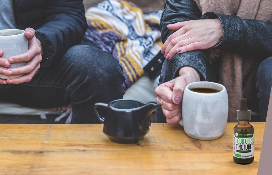 We wanted to compare CBD vs. CBG to help people understand how these two potent cannabinoids are similar, yet different. Photo: Two people in warm clothes share mugs of tea, while a teapot and a bottle of Every Day Optimal rests nearby.