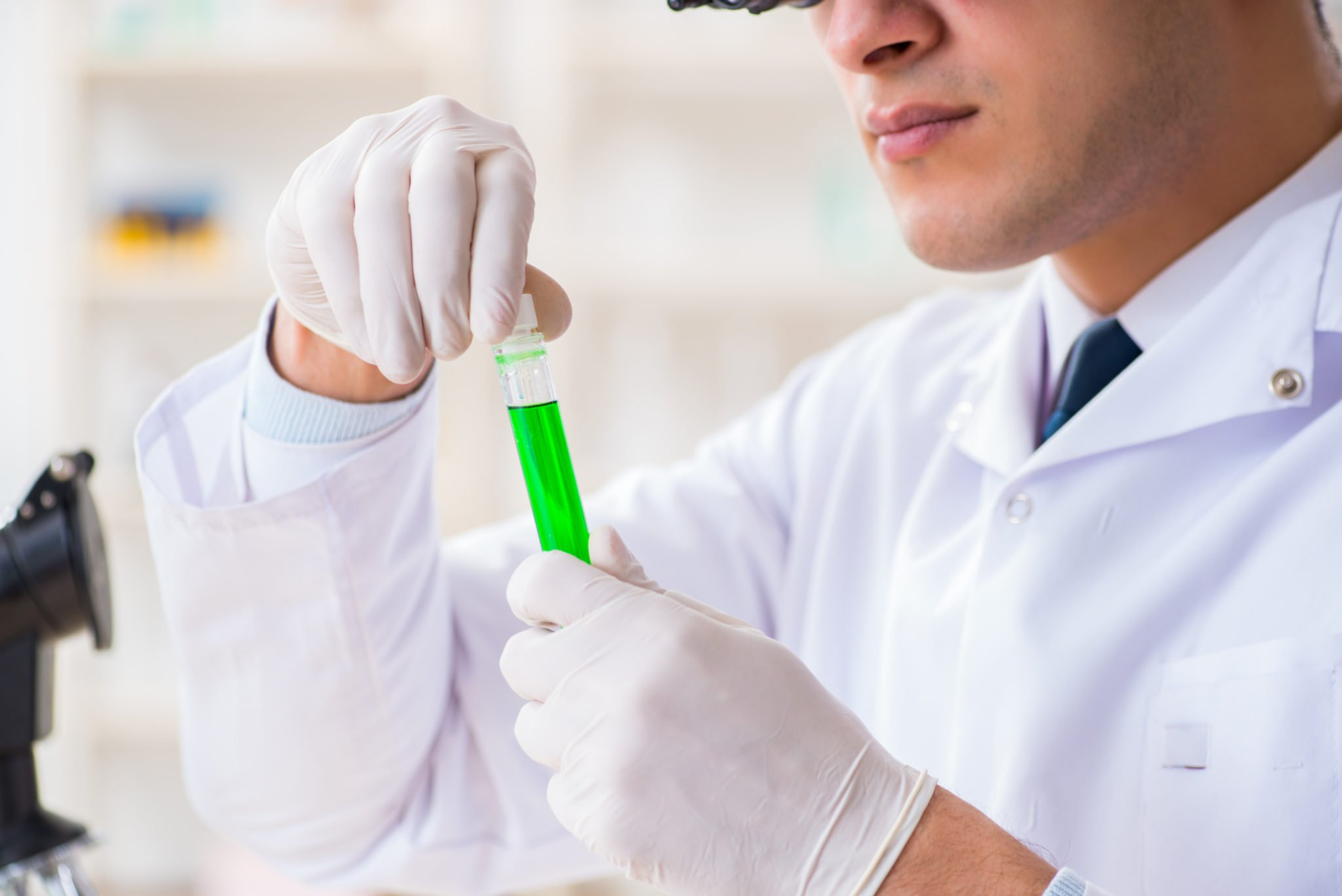 Increased federal oversight could help improve the quality of cannabis testing labs, and cannabis and hemp products in general. Photo: A scientist in gloves and a white lab coat examines a test tube of green liquid, with a microscope nearby.