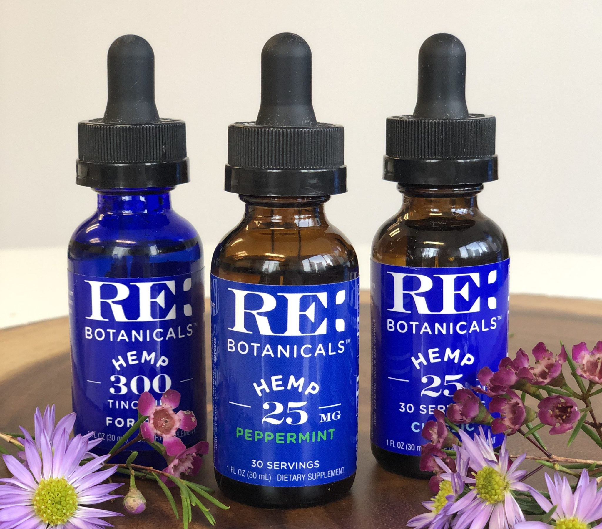 RE Botanicals Hemp Tincture tastes great, and left our reviewers feeling relaxed. Photo: RE Botanicals Hemp Tincture bottles on top of a wooden surface decorated with flowers.