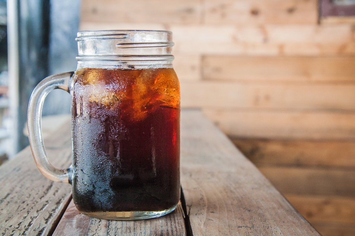 Our hemp oil cold brew recipe is easy, delicious, energizing, and even good for you. Photo: A mason jar-style mug of cold brew coffee with ice cubes rests on a rustic wooden counter.