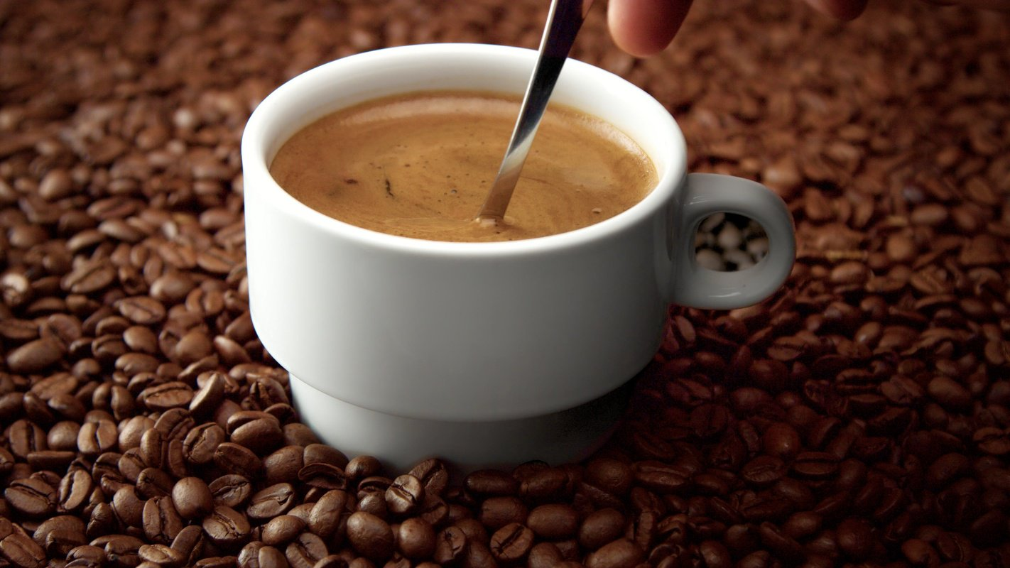 We think hemp seed oil tastes better, and offers unique benefits over butter or coconut oil. Photo: A spoon stirring a coffee cup on a bed of coffee beans.