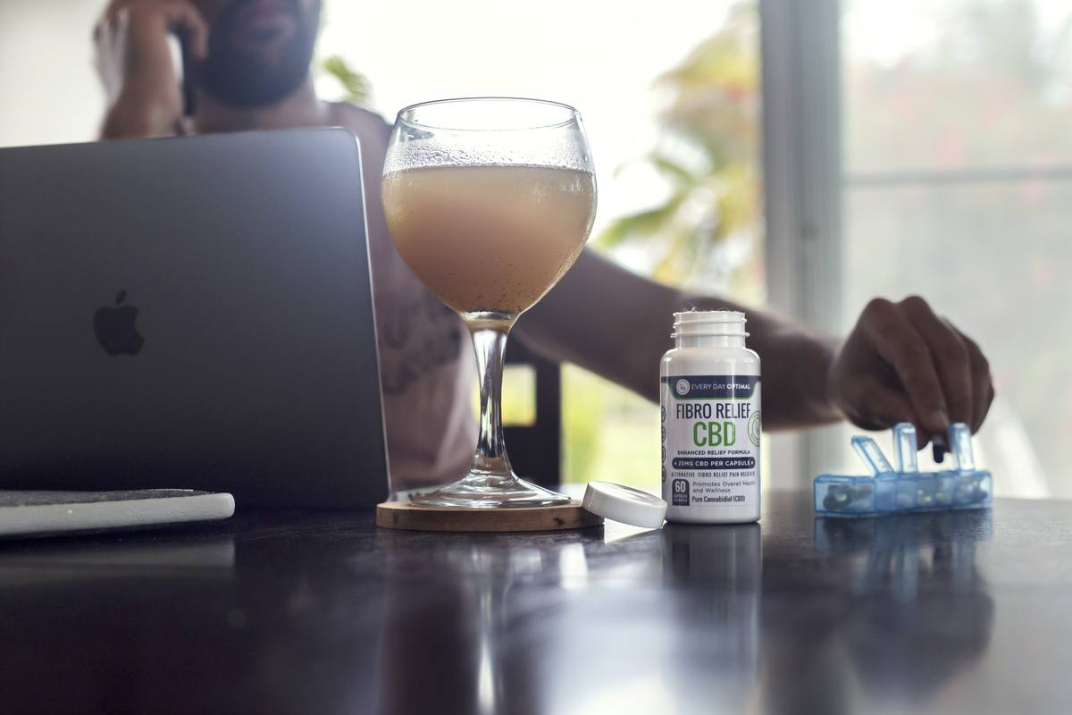 Combined with other forms of treatment, CBD for fibromyalgia is a promising option for relief. Photo: A person seated at a MacBook takes pills from a pill organizer. Nearby is a glass of juice and Every Day Optimal Fibro Relief CBD.