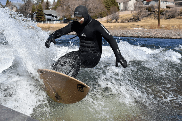 Photo: A surfer in a wetsuit rides a hemp surfboard.
