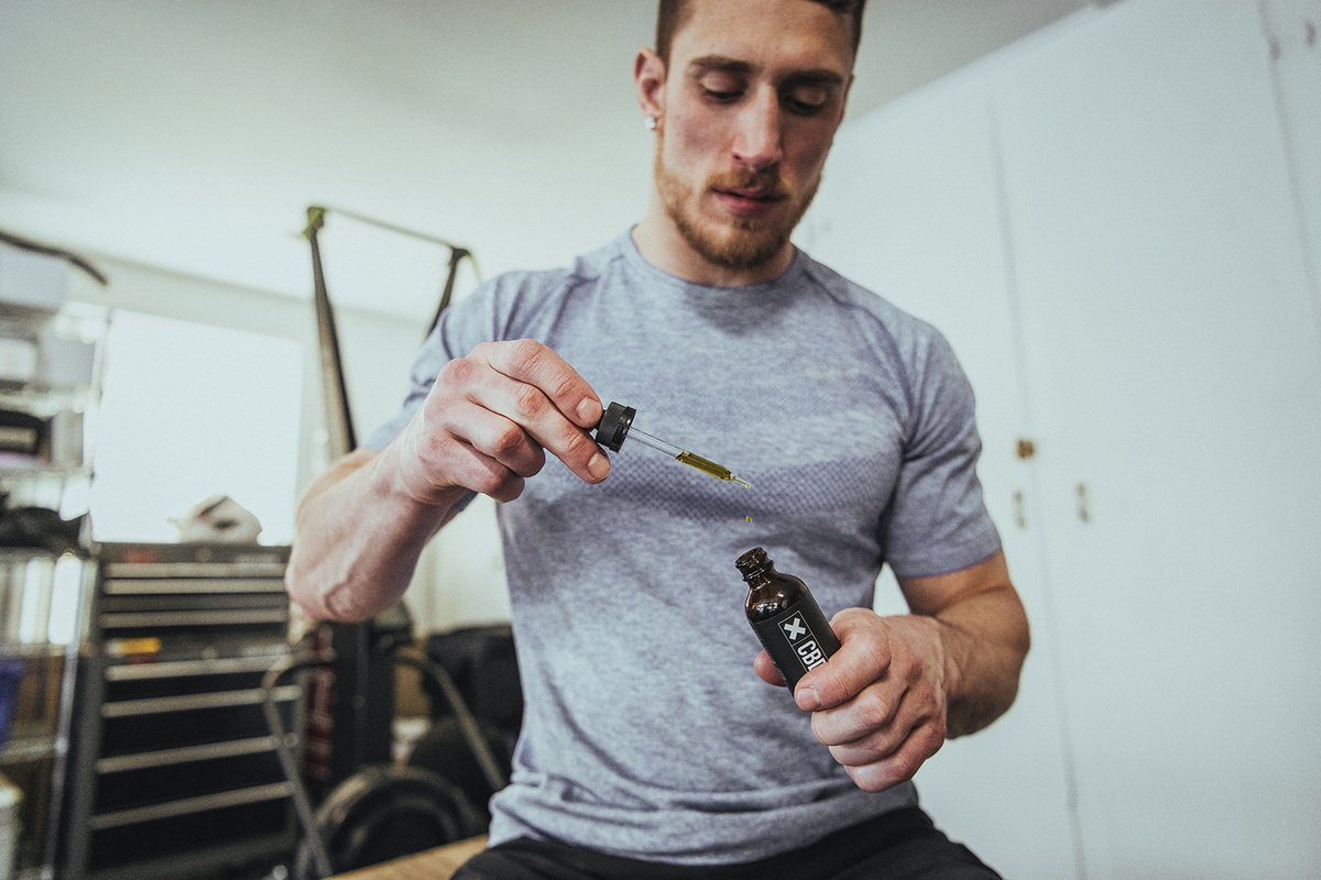Athletes use CBD for recovery to reduce soreness after workouts, promote deeper sleep, and more. Photo: A man in gray workout clothes takes XWERKS CBD after exercise.