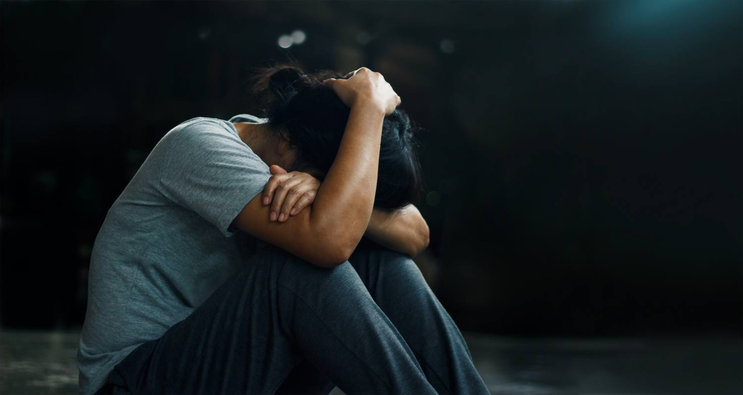 A new study of CBD and PTSD offered promising evidence. Photo: A woman seated in a fetal position rests her head on her knees.