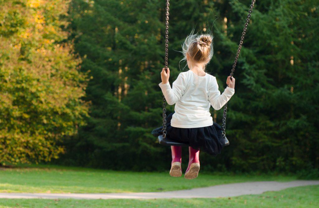 Seen from behind, a girl swings on a swingset alone outdoors. Numerous factors contribute to ADHD, including both environmental and genetic contributors.