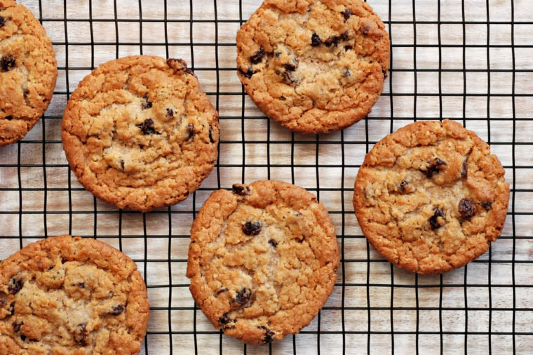 Freshly baked oatmeal raisin cookies on cooling rack over rustic wood background. Closeup from above with natural directional lighting.