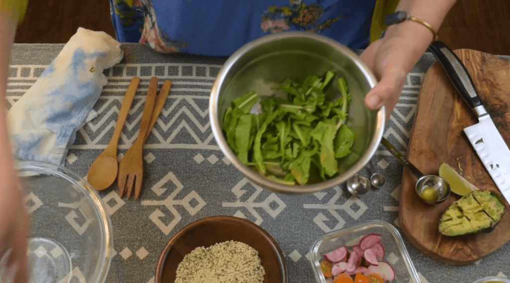 Video screenshot shows Drew assembling the hemp seed salad, with arugula in her bowl, and hemp hearts, strawberries, avocado and other ingredients ready nearby.