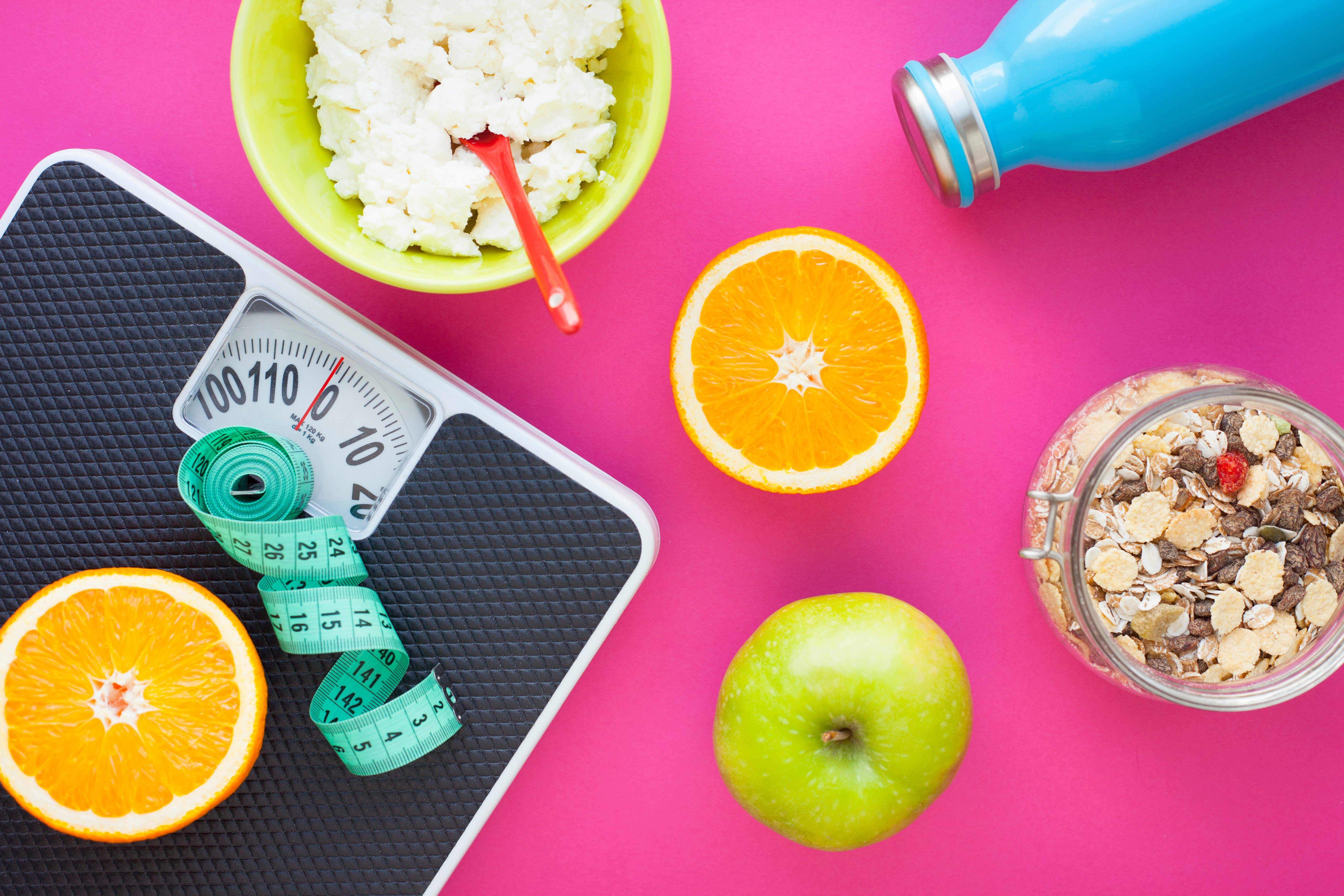 Fruits, curd, measuring tape, water and muesli on the pink background. Weight loss, diet controlled healthy food concept background. Top view, close up.