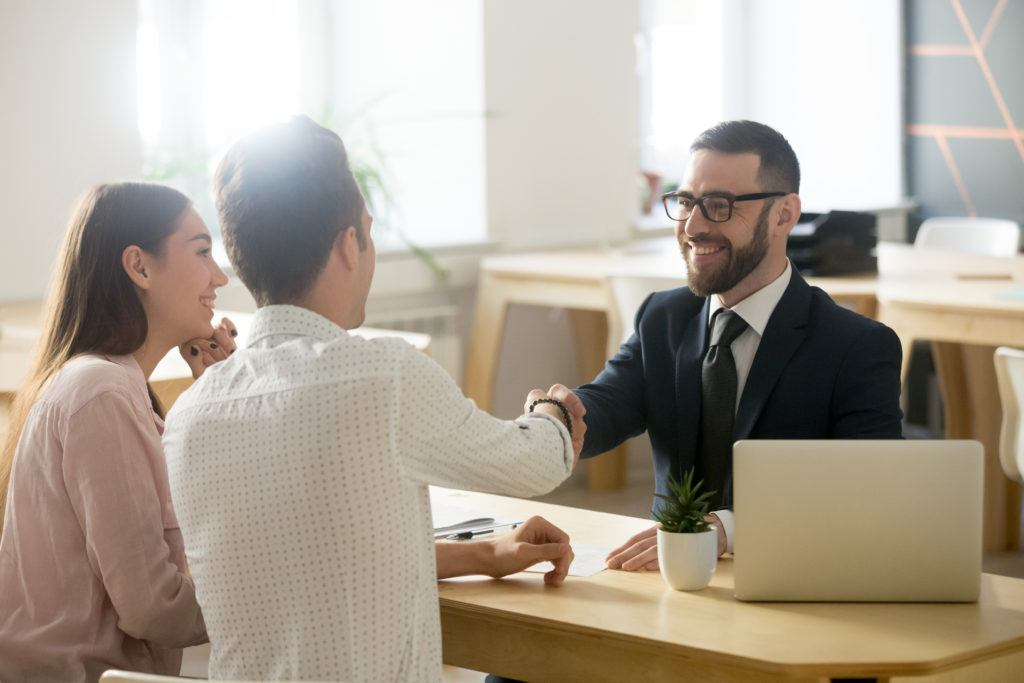 In the Ministry of Hemp podcast we talked about hemp insurance and issues around banking and hemp. Photo: A man and woman meet with a bearded financial advisor in a suit in an office. Between them is a desk with a laptop and a cactus in a coffee mug. The two men are shaking hands.