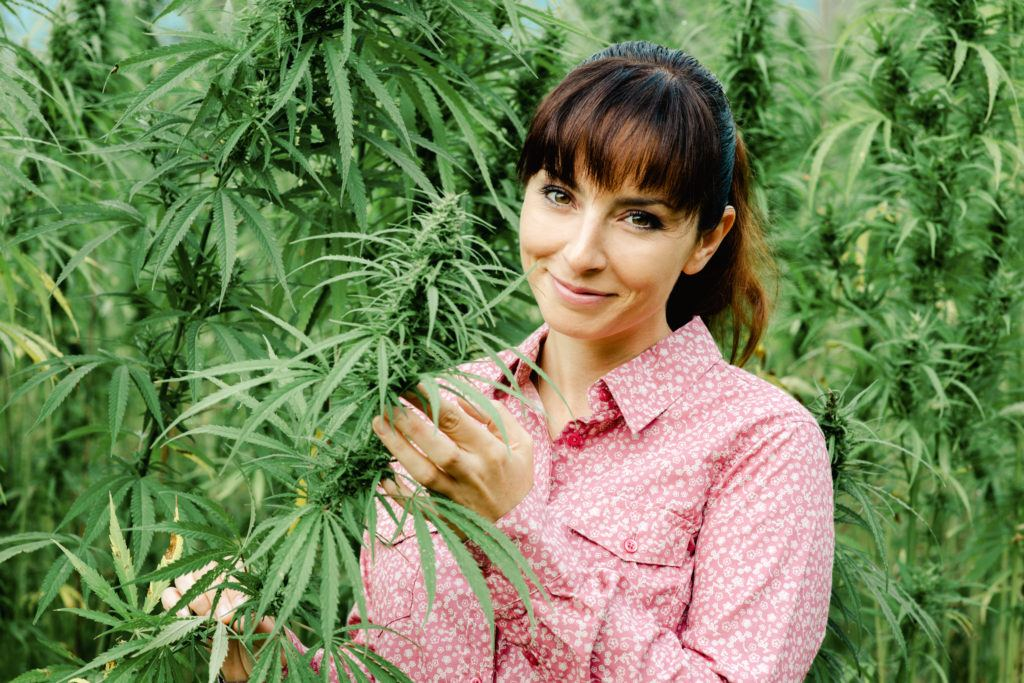 On the Ministry of Hemp Podcast, we're beginning a series on the women of hemp. Photo: A smiling young woman stands in a hemp field, wearing a pink button down. One hand holds part of a leafy hemp plant.