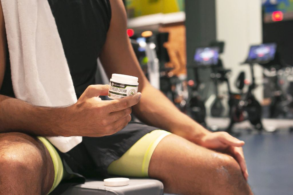 A person sitting in a gym applies Every Day Optimal CBD cream after a workout.