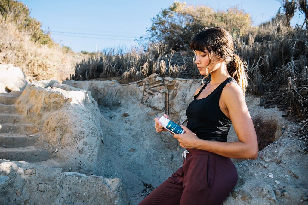 Photo: A jogger leans against a natural stone wall while holding Vitagenne CBD Cooling Cream.