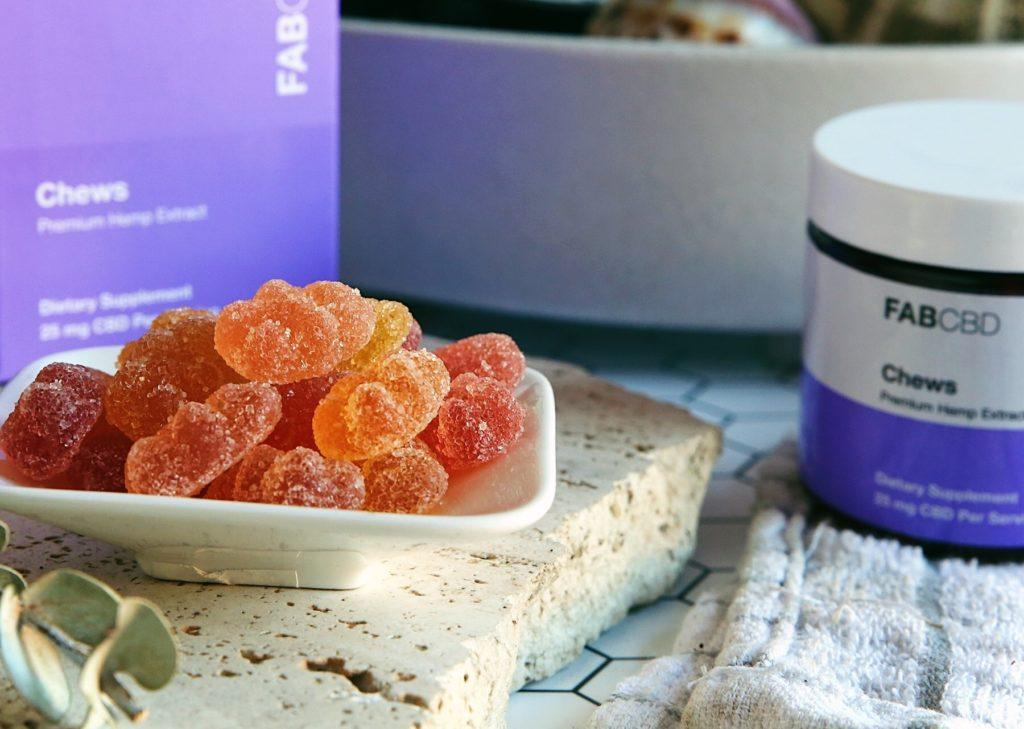 Fab CBD Chews in a small platter near product in a kitchen, along with the box and jar.