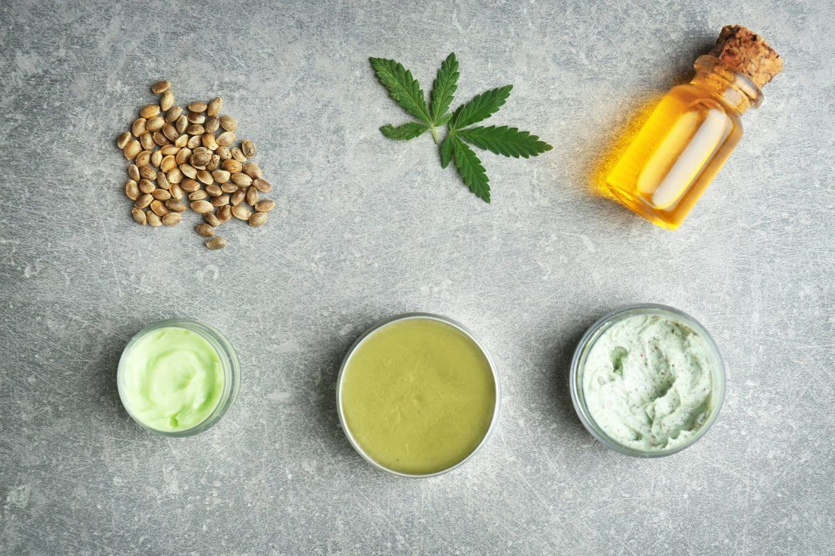 A variety of topical CBD products seen with some hemp seeds, a hemp leaf, and a vial of essential oil.