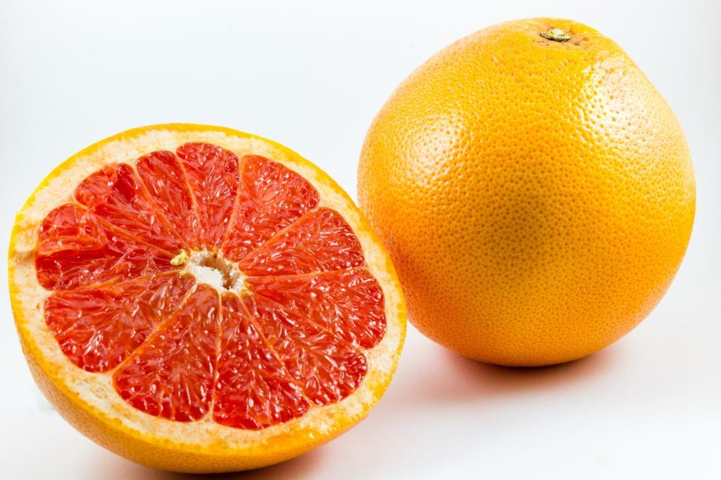 How is CBD like grapefruit? Both could interact with some pharmaceutical drugs. Photo: Two grapefruits, one whole and one sliced in half to show the inside.