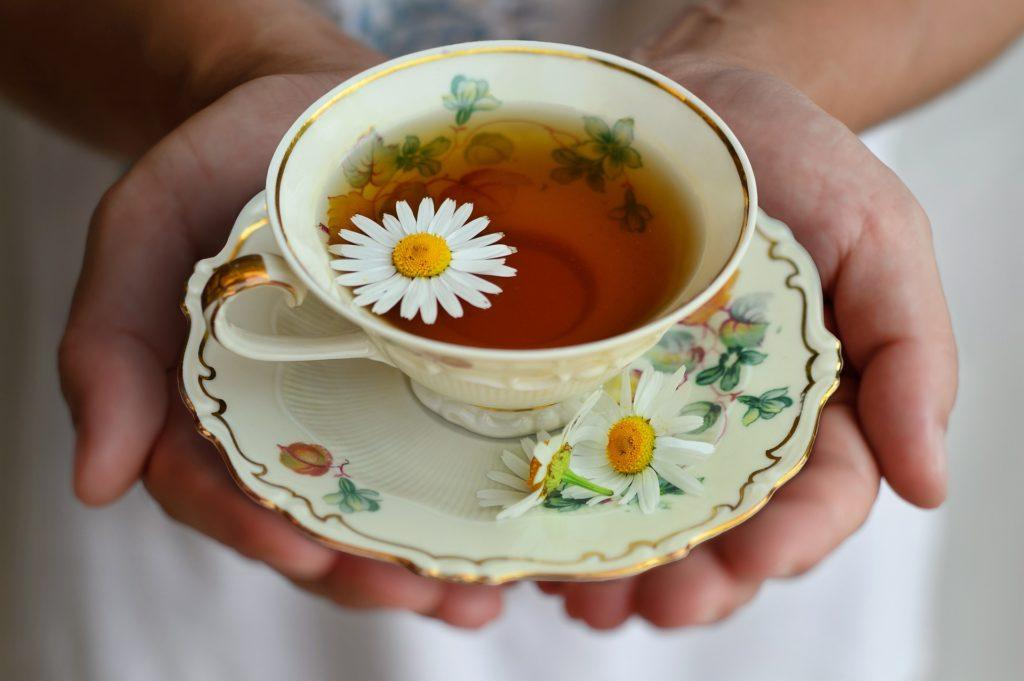 Chamomile could be one of the best known natural sleep aids. Photo: A person holds a teacup and saucer in cupped hands. In the cup is chamomile tea, garnished with fresh chamomile flowers.