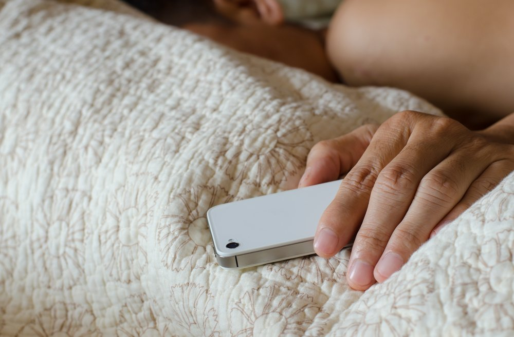 man sleeping in bed while holding his cellphone