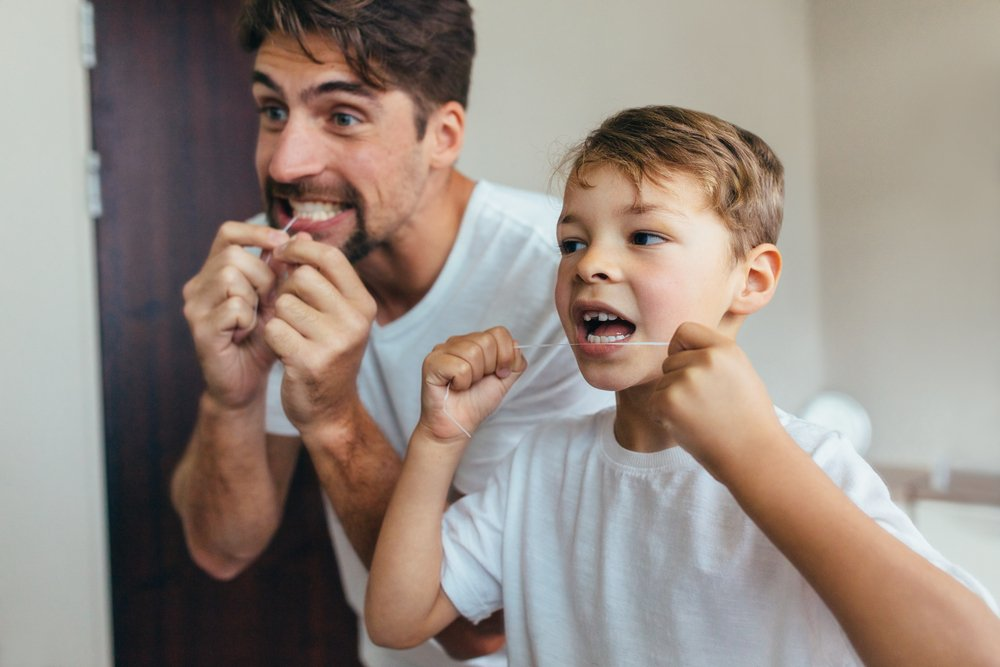 father and son flossing teeth