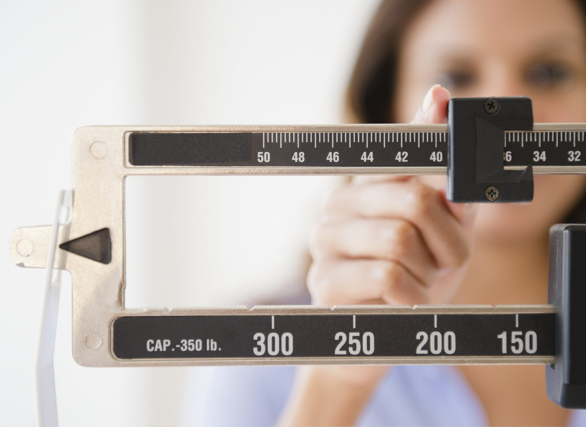 signs your body is in trouble | woman adjusting scale