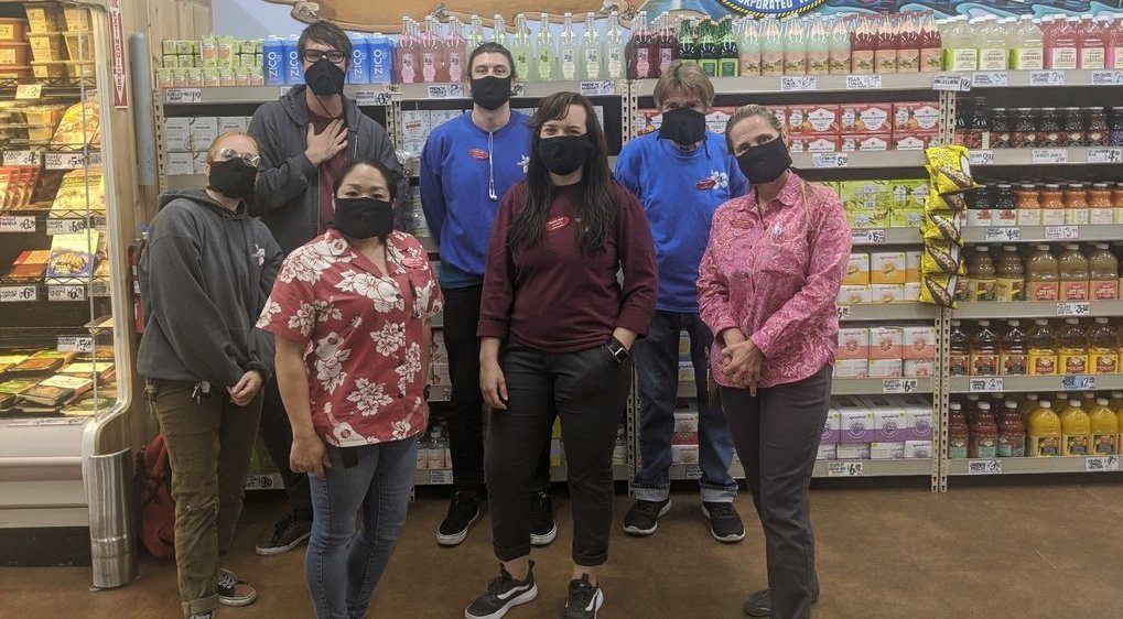 Workers at a Trader Joe's pose in hemp masks created by iLoveBad and The Hemp Cooperative.