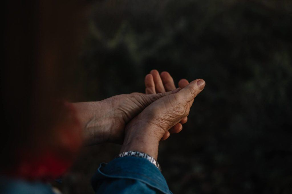Photo: A person rubs their hands in relief from pain.