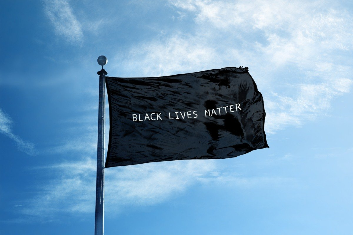 The hemp industry needs to take a stand for black lives. Photo: A Black Lives Matter flag on a flag pole against a partly cloudy blue sky.