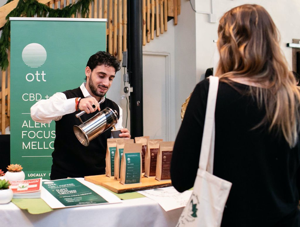 Our podcast guest, Alwan Mortada, pours a sample of his CBD coffee at a holiday market.
