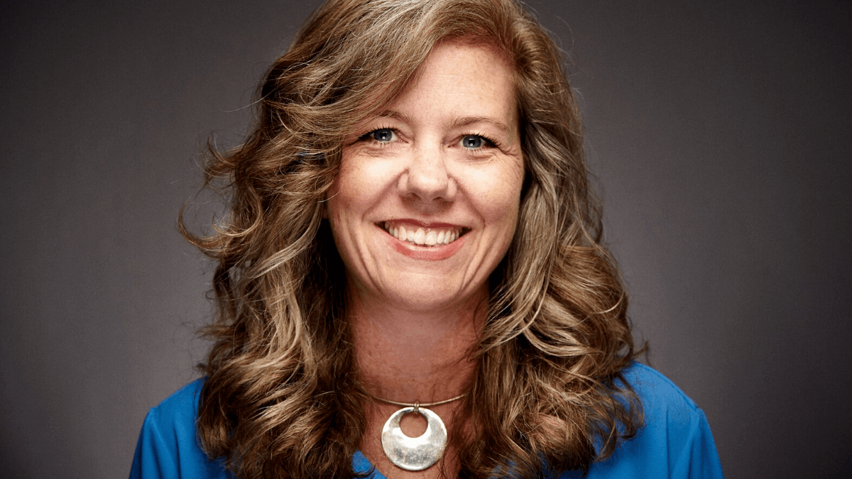 Photo: A picture of Eloise Theisen, a white woman with brown hair in ringlets below her shoulders, in a blue blouse and wearing a circular necklace. Theisen is a cannbis nurse and helps run the Cannabis Nursing Association.