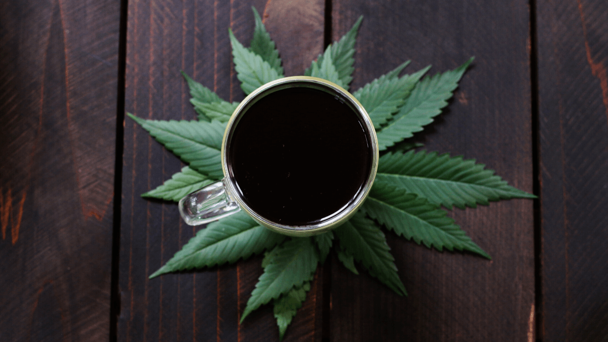 Science still has a lot to learn about combining CBD with caffeine. Photo: A cup of dark coffee posed atop hemp leaves on a wooden tabletop.